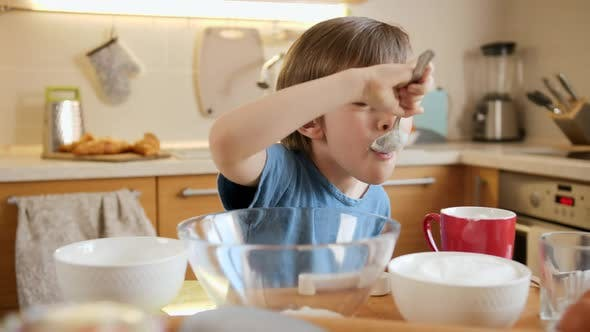 Funny Laughing Little Boy Eating Creme for Baking Pie with Spoon