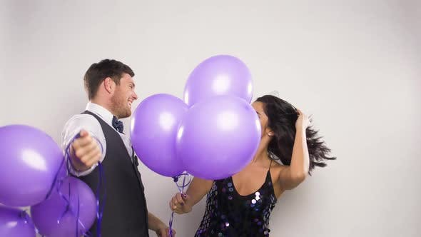 Thumbnail for Happy Couple with Purple Balloons Dancing at Party