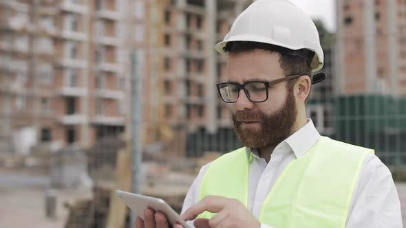 Thumbnail for Portrait of a Successful Young Businessman Wearing a White Helmet in a Suit Working with Tablet