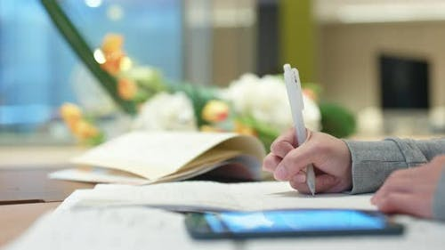 Woman study the note on paper with mobile phone at library