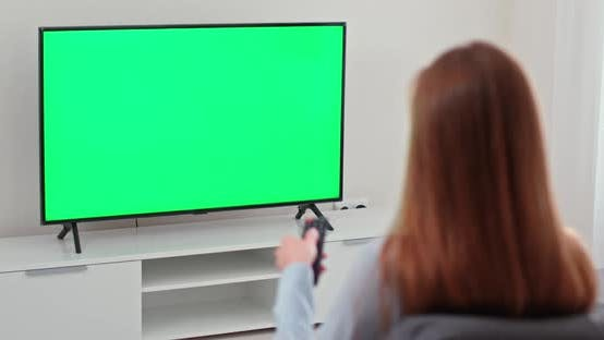 Girl Is Sitting on the Sofa in the Living Room and Watching TV, Green Screen, the Girl Switches