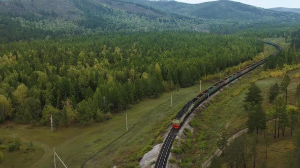A Cargo Train Is Carrying Coal Through the Woods
