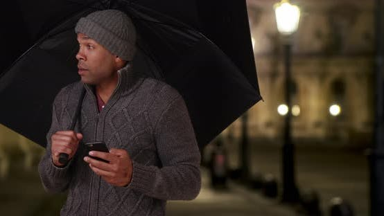 Thumbnail for African-American man standing outside with umbrella on cold night in Paris