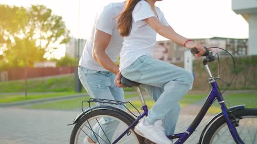 Dad is Teaching Daughter How to Ride Bicycle at Sunset