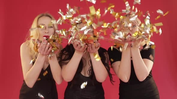 Thumbnail for Three Women in Black Dresses Blowing Confetti in Studio