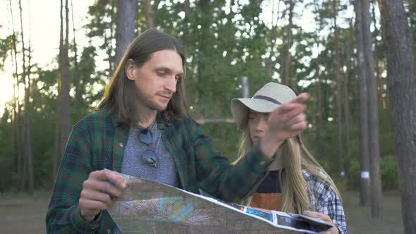 Thumbnail for Hipster Tourist Couple in Plaid Shirts Choosing the Way To Go on the Background of Forest