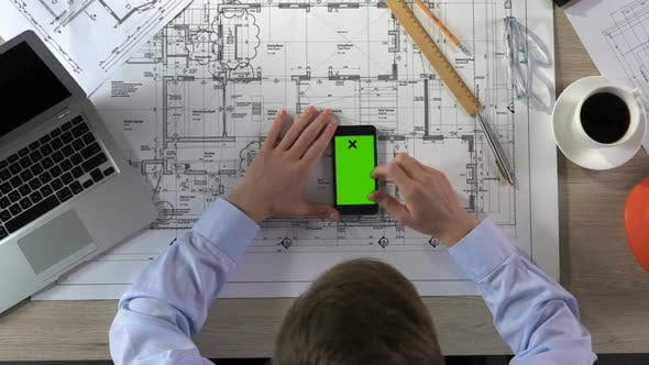 Thumbnail for Male Architect Scrolling on Smartphone With Green Screen at Workplace, Top View