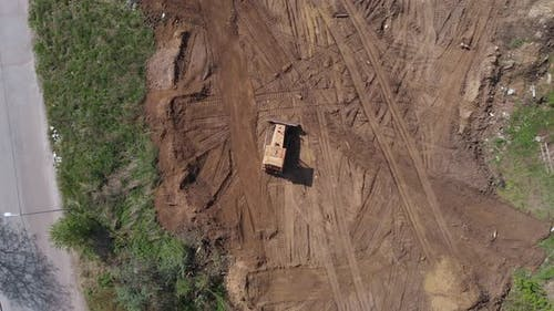 Top aerial view of bulldozer driving on further construction site