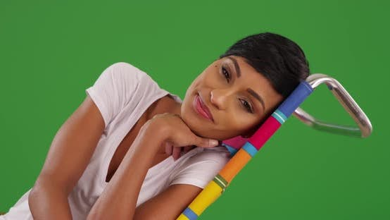 Thumbnail for Black female lounging, looking at camera with joyful smile on green screen