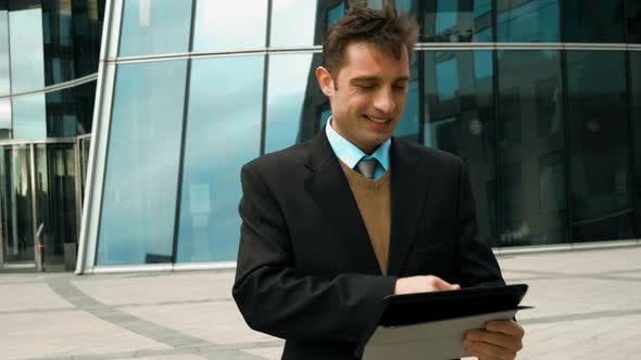 Thumbnail for Businessman Using Electronic Tablet Outside a Building