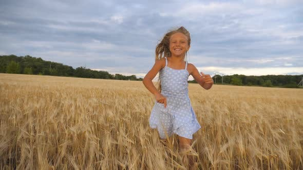 Beautiful Happy Girl with Long Blonde Hair Running To the Camera Through Wheat Field. Little Smiling