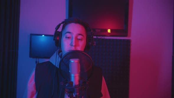 Thumbnail for A Man in Hoodie Rapping Through the Pop-filter in the Microphone - Recording His Track