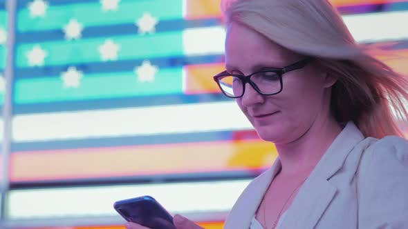 Cover Image for Business Woman Uses a Smartphone on the Background of a Large American Flag on the Famous Times