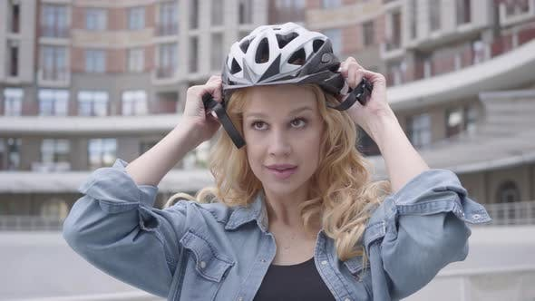 Thumbnail for Portrait Cute Blond Woman Putting a Bike Helmet on Her Head and Riding Her Bicycle