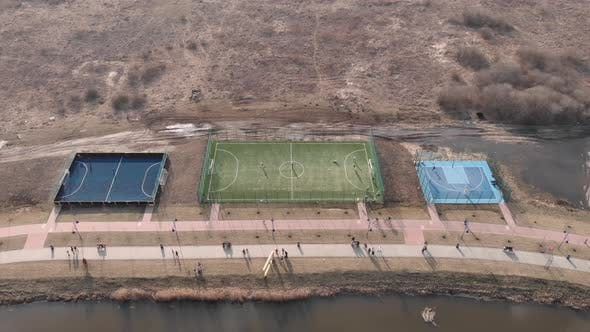 People spending holidays on fresh air, walking on promenade along river with football field
