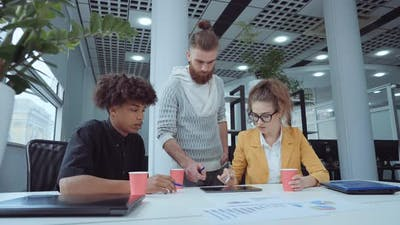 Startup Team Discussing Company Progress in Office