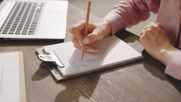 Thumbnail for Hände einer Geschäftsfrau, die mit Bleistift auf Papier schreibt