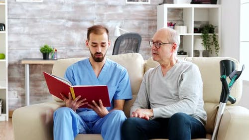 Social Worker Reading a Book To an Old Disabled Man in Nursing Home
