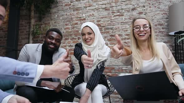 Cover Image for Multi-Ethnic Group of Business People with Arabic Female Leader in Hijab Showing Thumbs Up Gesture