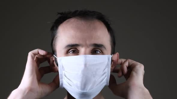 Caucasian man wearing a white medical mask for protection against contagious disease, coronavirus