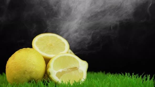 Thumbnail for White smoke falling on organic yellow lemons on grass surface