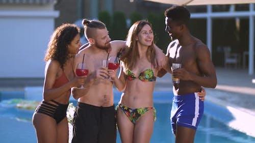 Joyful Multiracial Friends Drinking Juice By Pool