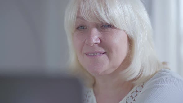 Thumbnail for Close-up Face of Attractive Mature Caucasian Woman Looking at Laptop Screen and Smiling