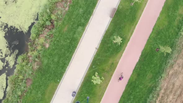 Cover Image for Triathlete female is doing cycling training on cycle path in park top aerial view