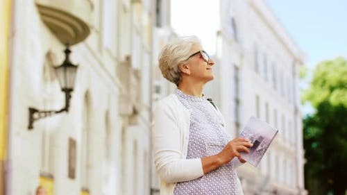 Senior Woman or Tourist with City Guide on Street