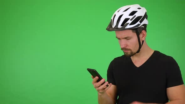 Thumbnail for A Young Handsome Cyclist Works on a Smartphone, Then Smiles at the Camera - Green Screen Studio