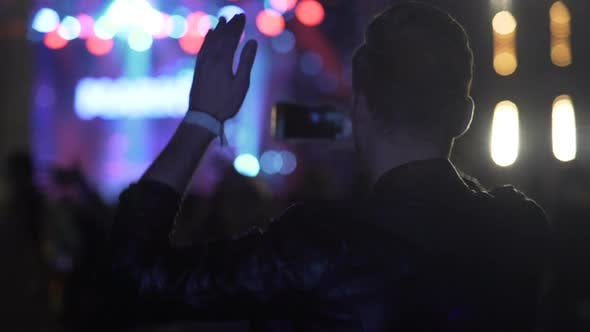 Thumbnail for Young Male Dancing, Waving Hands and Shooting Video on Cellphone at Concert