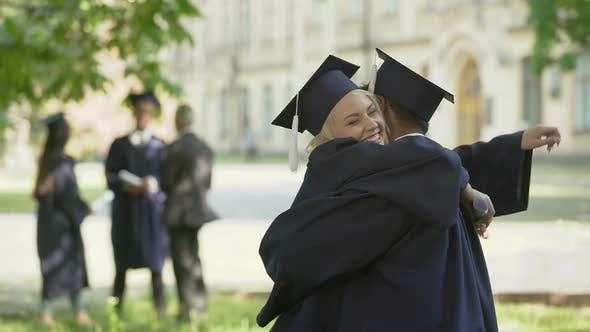 Thumbnail for College graduates having conversation, hugging each other, university friendship