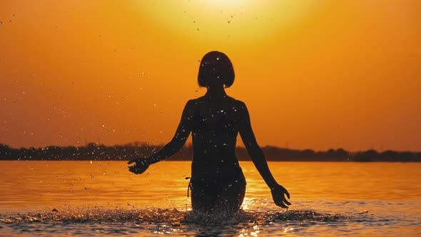 Thumbnail for Silhouette of Woman at Sunset Raises Hands Up and Creating Splashes of Water