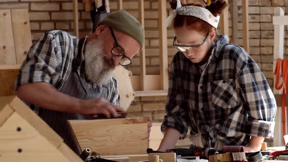 Thumbnail for Senior Woodworker and His Granddaughter in Workshop