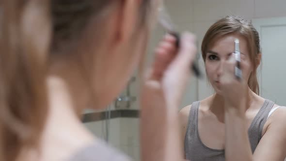 Thumbnail for Young Woman Putting Makeup on Face in Mirror