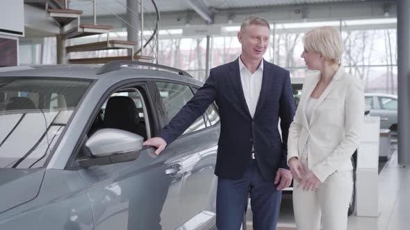 Confident Caucasian Businesswoman Choosing Car in Dealership. Smiling Dealer Consulting Client in