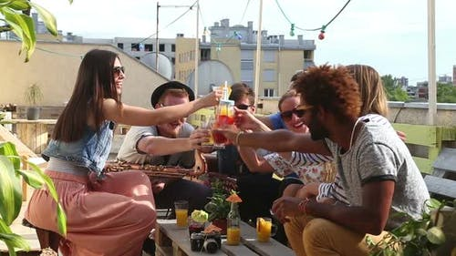 Cheerful multi-ethnic friends laughing and toasting with cocktails at rooftop