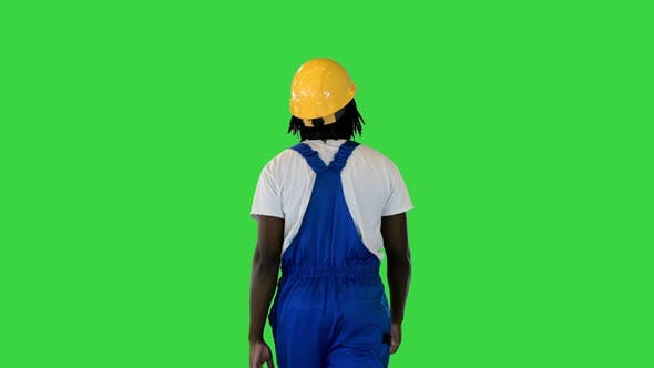 Handyman in a Helmet and Working Suit Walking on a Green Screen Chroma Key