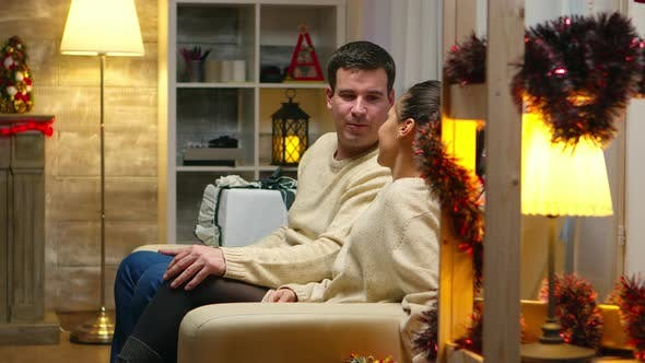 Thumbnail for Romantic Young Couple Sitting on the Couch on Christmas Day