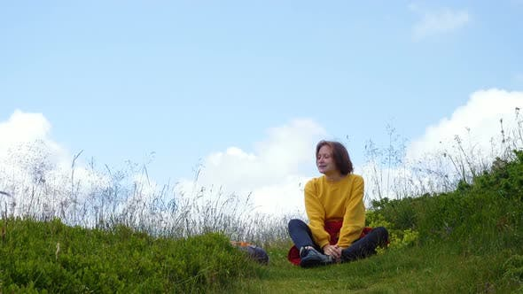 Thumbnail for Girl Hiker Sitting On A Grassy Hill