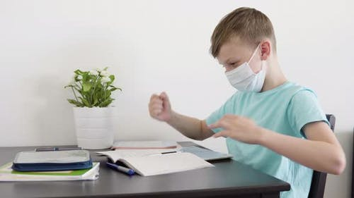 A Young Boy in a Face Mask Checks His Homework for School and Celebrates at a Table at Home
