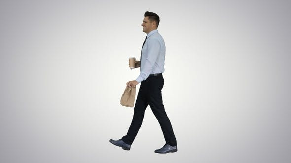 Businessman walking with take away coffee and paper bag