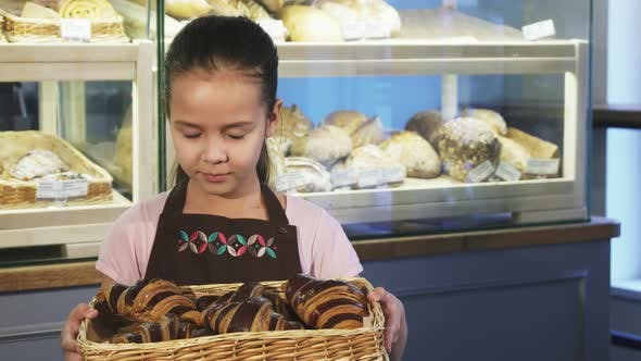 Thumbnail for Cute Little Girl in an Apron Working at the Bakery Holding a Basket with Pastry