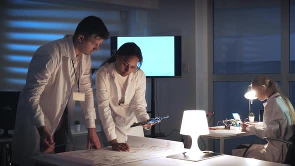 Thumbnail for Man and Woman in Lab Coats Working in Electronics Lab with Motherboard and Control Electronics