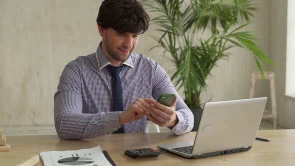 Man Using Smartphone While Sitting on Office and Using Phone