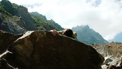 Happy Man Climbs a Boulder and Raises His Hands Up. Bouldering in the Mountains