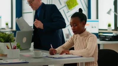 African Businesswoman Analysing Report and Looking at Camera Smiling
