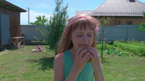 Girl Eating Burger Backyard