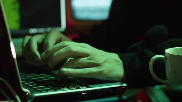Professional Hacker Typing on Keyboard at Night Closeup of Man Hands Trying to Break Password Using