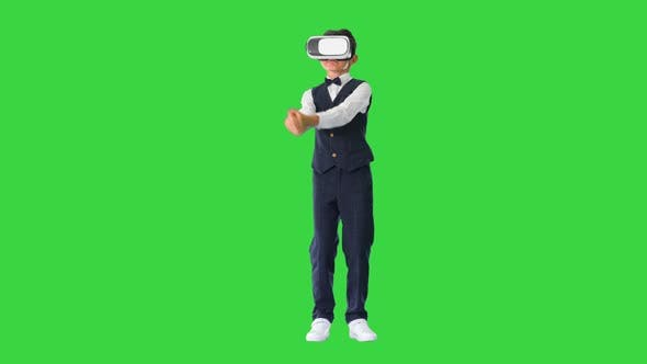 Excited Boy in Formal Wear Playing the Sword Game in Virtual Reality Goggles on a Green Screen